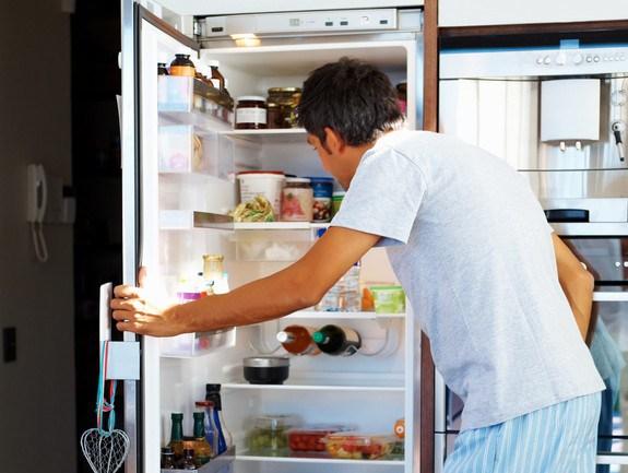 man finding items in fridge